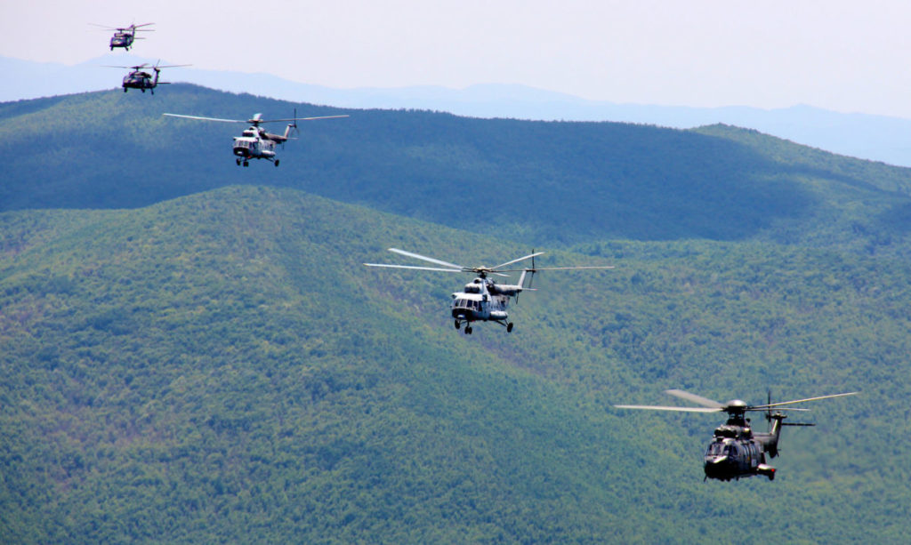 helicopters floating above mountain haze