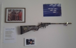Photo of gun and pictures on wall