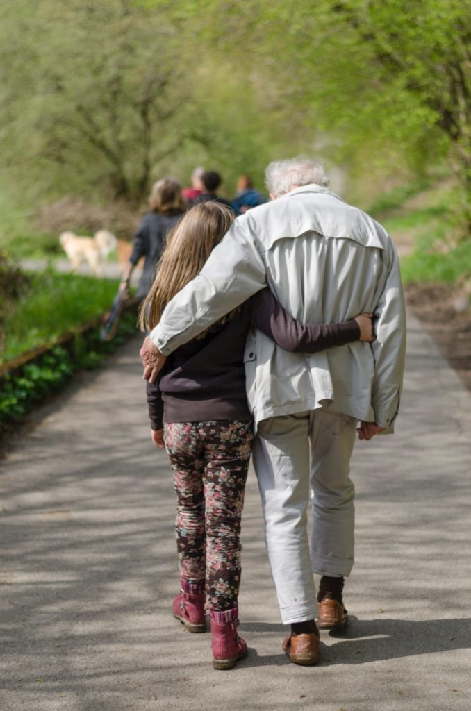 Photo of old man walking with girl