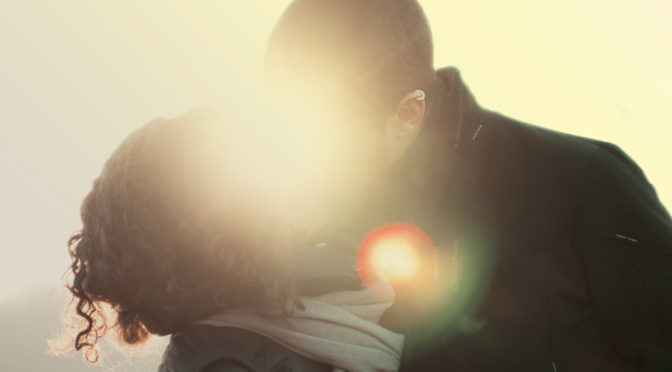 man and woman kissing in sunbeam