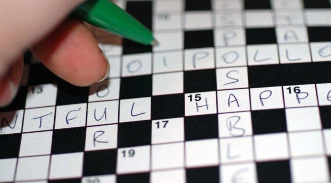 Photo of hand holding pen filling in crossword