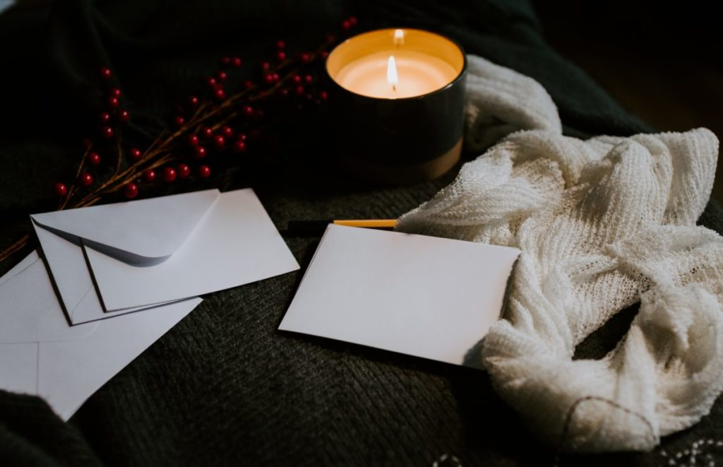 Photo of lit candle and envelopes