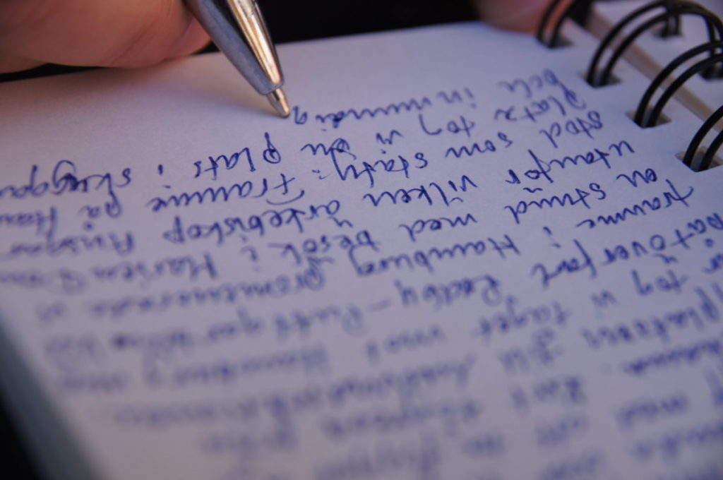 Photo of pen writing in notebook