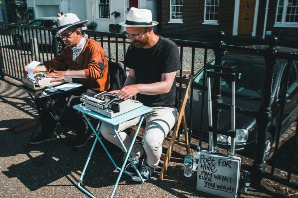 2 men typing with Poet for Hire sign
