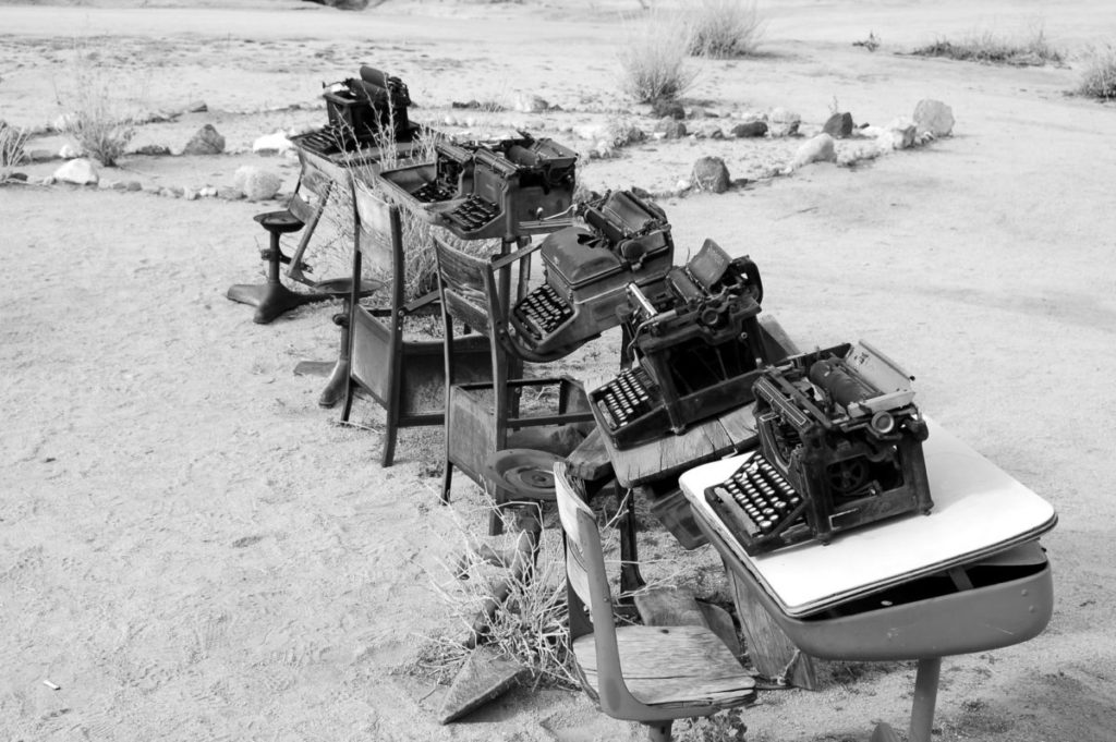Black and white photo of typewriters on desks in desert