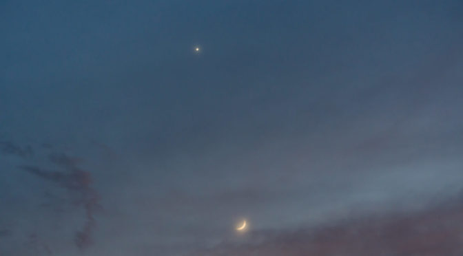 crescent moon and venus in pale blue sky