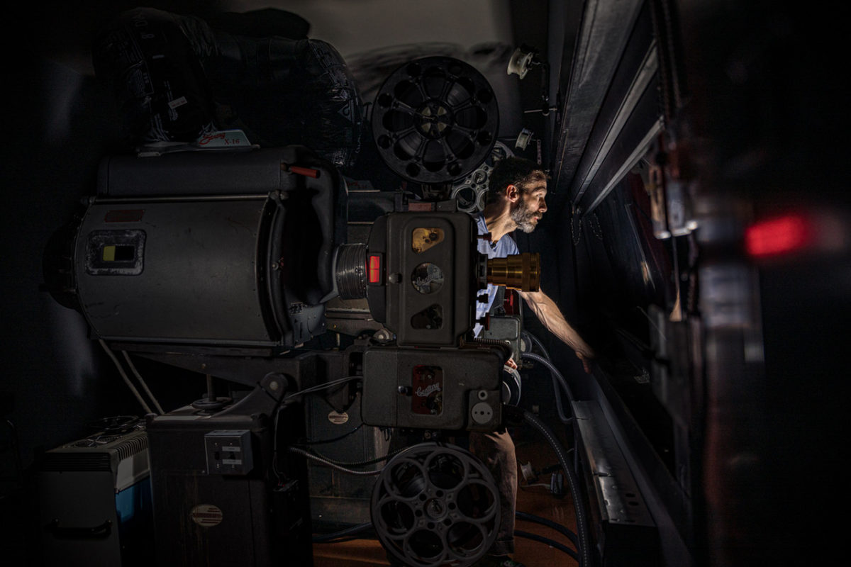 Man in projection booth next to projector
