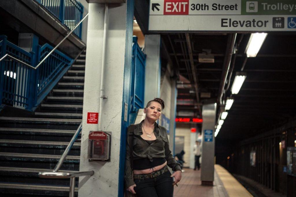Woman standing in metro, near train
