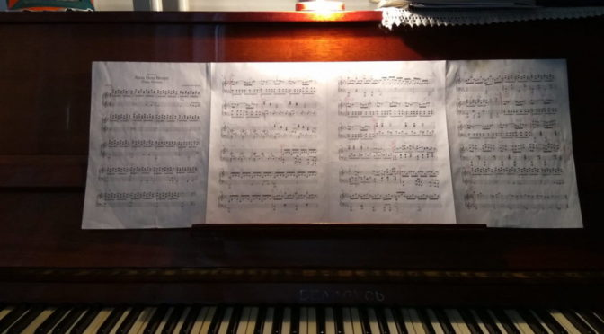 Photo of open piano with music sheets