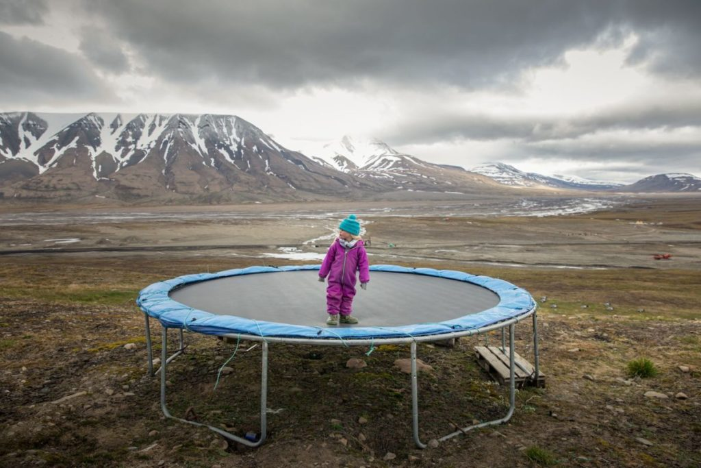 Photo of child on trampoline in front of snowy mountains