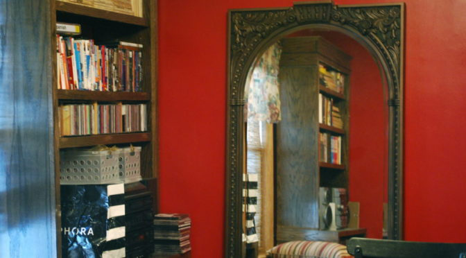 Picture of mirror by bookcase
