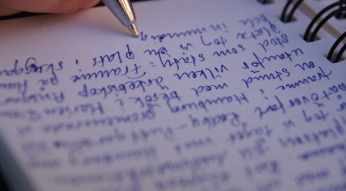 Photo of pen writing on paper